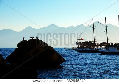 Mediterranean seascape image of people sailing on tour boat over high mountains with sunny sky in Antalya, Turkey