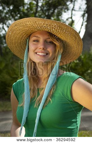 Young Woman In Green Shirt And Straw Hat