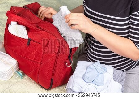Unrecognizible Pregnant Caucasian Woman In Striped T-shirt Packing Big Red Diaper Bag To Maternity H