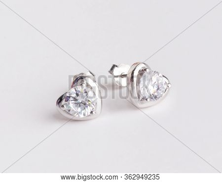 A Pair Of Beautiful 925 Sterling Silver Earrings In Heart Shape Decorated With Diamond Isolated On W