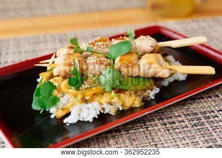 Yakitori chicken with rice on black plate, Japanese dish