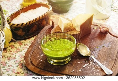 A Glass Bowl With Homemade Pesto Sauce On A Wooden Table With Grated Cheese And Slices Of Parmesan C