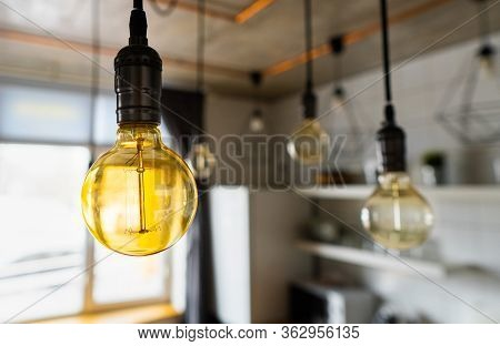 Close-up Of Incandescent Light Bulbs Hanging In Modern Kitchen. Decorative Antique Edison Light Bulb
