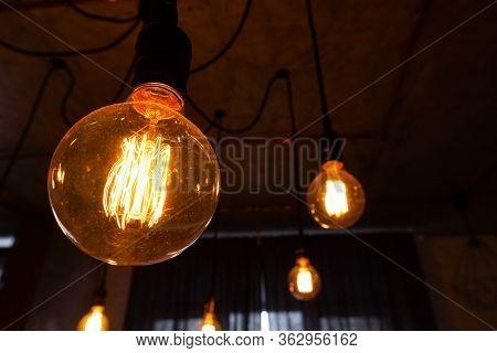 Inefficient Filament Light Bulbs Waste Electricity. Close-up Of Big Incandescent Light Bulb Hanging