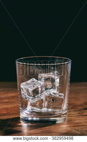 Crystal Whiskey Glass With Ice Cubes On A Wooden Table.