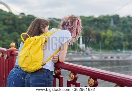 Portrait Of Two Teenage Girls Standing With Their Backs On Bridge Over River, Girls Friends Enjoying