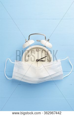 Medical Protective Mask And Alarm Clock On A Blue Bright Wooden Background. The Concept Of Preventiv