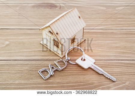 dad message shaped key chain with house symbol and keys on wooden background