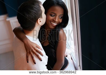 Happy, Loving Young Interracial Couple Cuddling While Standing Near The Window. Beautiful Black Girl