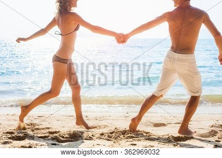 Young happy couple run on the tropical beach. Happy man and woman holding each other's hands and running on the beach