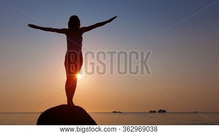 Woman stands on the rock with stretched hands and enjoys sunset