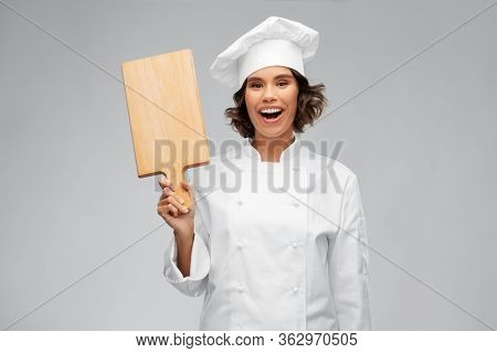 cooking, culinary and people concept - happy smiling female chef in toque with wooden cutting board over grey background