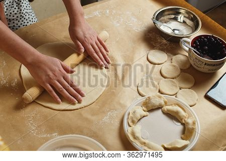Woman Hands Rolling Out Dough In Flour With Rolling Pin In Her Home Kitchen