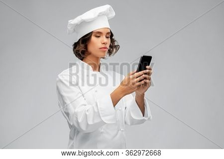 cooking, culinary and people concept - female chef in toque with smartphone over grey background