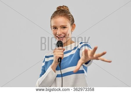 music and people concept - smiling teenage girl in pullover with microphone singing over grey background