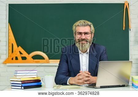 Teach And Inspire. Senior Teacher Sit At Desk. Bearded Man Back To School. Formal Education. Educati