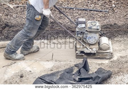 Workman Operating A Power Plate Compactor On Muddy Ground