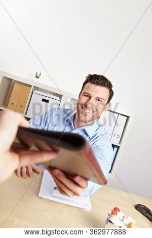 Applicants give their application folder to HR professionals in the office