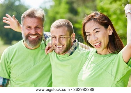 Happy young people in green shirts as an environmentalist team