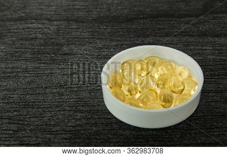 Yellow Soft Shell D-vitamin Capsule In Bowl. Fish Oil Capsules With Omega 3 And Vitamin D On Dark Wo