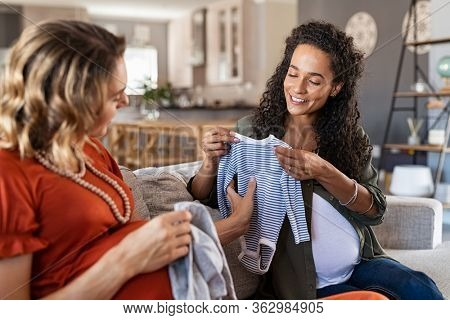Happy pregnant woman talking with friend. Multiethnic pregnant friends sitting on sofa and looking at baby shower gifts. Female friend giving to mixed race pregnant woman a present for the new baby.