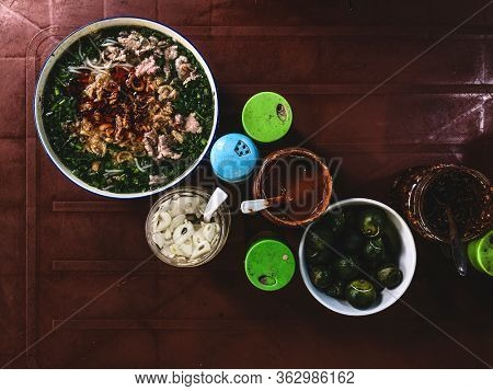 Top view on a traditional pho bo on a dark table. Pho bo is Vietnamese fresh rice noodle soup with beef, herbs and chili. Vietnam's national dish