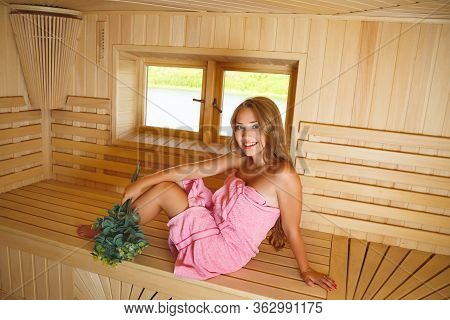 The Lovely Girl In A Sauna Smiles. A Bath Broom From Birch Branches In A Hand