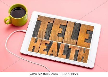 telehealth - word abstract in vintage letterpress wood type on a digital tablet, health, healthcare and telecommunication technology concept