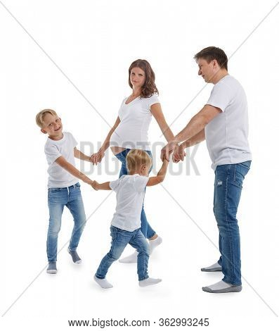 Pregnant mother and father with two sons on white background. Parents with children are playing: holding hands in circles and walking or dancing around. Happy friendly family. Concept of parenting