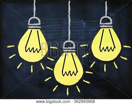 Three yellow light bulb on balackboard