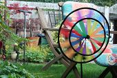 A colorful miniature windmill spinning in the breeze on a low shutter speed. poster