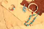 Assortment of Native American silver turquoise and coral jewelry displayed on pieces of soft and pliable buckskin and leather. poster