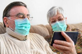 Coronavirus. Stay At Home, Lifestyle.cheerful Elderly Couple Sitting On A Sofa On A Quarantine At Ho