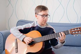 Learning To Play The Guitar. Music Education. Boy Playing Acoustic Guitar. Serious Teenager In Glass