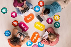 Above view of internet users sitting in circle among social media activity tags and icons and surfing net on devices