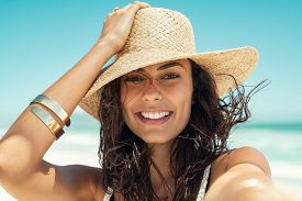 Close up face of happy young woman with straw hat enjoying her summer holidays. Portrait of beautiful latin girl relaxing at beach and looking at camera. Carefree brunette beauty woman enjoy summer.