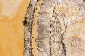 An Arid Wind Swept Patch Of Orange Dirt In A Dry Unused Waterway.