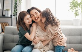 Happy mother's day! Mom and her daughters children girls are playing, smiling and hugging. Family holiday and togetherness.