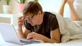 Young Man With Glasses Is Working From Home During Coronavirus Or Covid-19 Quarantine. Man Using Lap