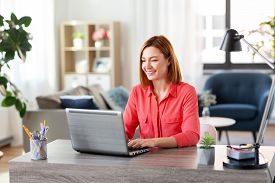remote job, technology and people concept - happy smiling young woman with laptop computer working at home office