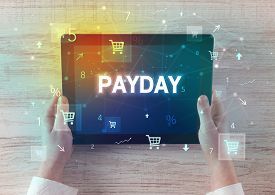 Close-up of a hand holding tablet with PAYDAY inscription, online shopping concept