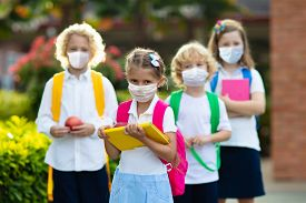 School Child Wearing Face Mask During Corona Virus And Flu Outbreak. Boy And Girl Going Back To Scho