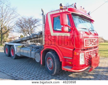 Front Side View Of Red Skip Truck With Hydraulic Arm
