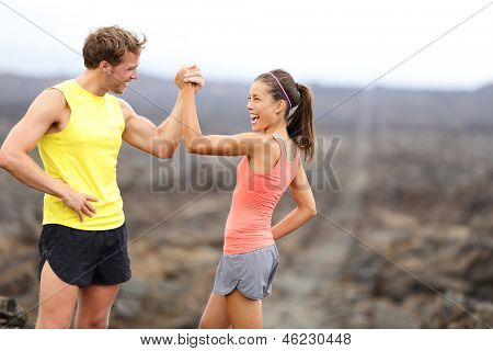 Fitness sport running couple celebrating cheerful and happy giving high five energetic and cheering. Runner couple having fun after trail cross-country running training. Asian woman, Caucasian man.