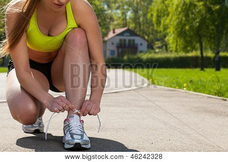 Beautiful young woman in fitness wear ties shoelaces outdoors