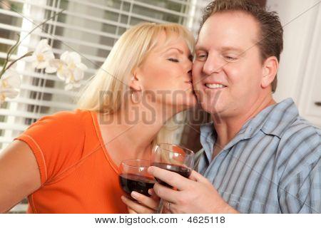 Kissing Couple Enjoying Wine Together