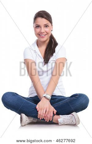 casual young woman sitting with legs crossed and holding them with both hands together. isolated on white background