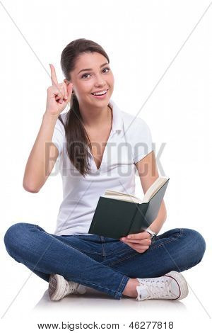 casual young woman sitting with legs crossed and having an idea while holding a book, pointing up while looking at the camera. isolated on white background