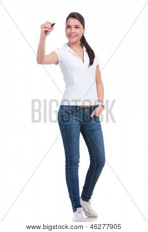 full length picture of a casual young woman writing on an imaginary screen and holding her other hand in the pocket. isolated on white background
