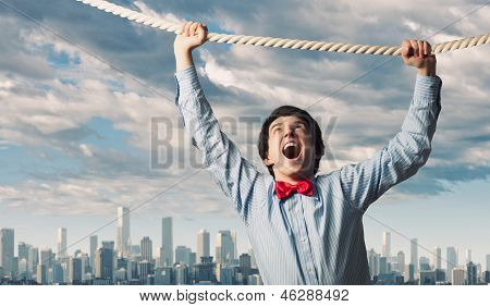 Businessman hanging on rope
